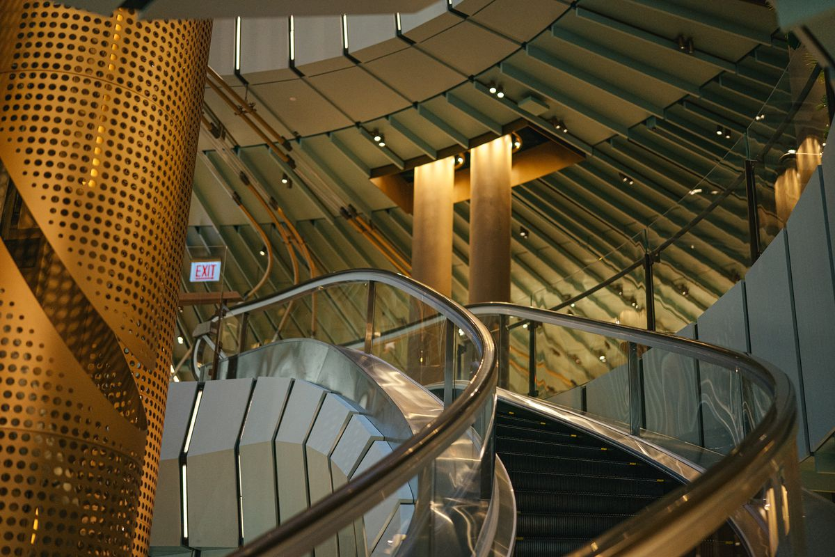 A view of the curved escalator, gold cylinder and teal panel roof.