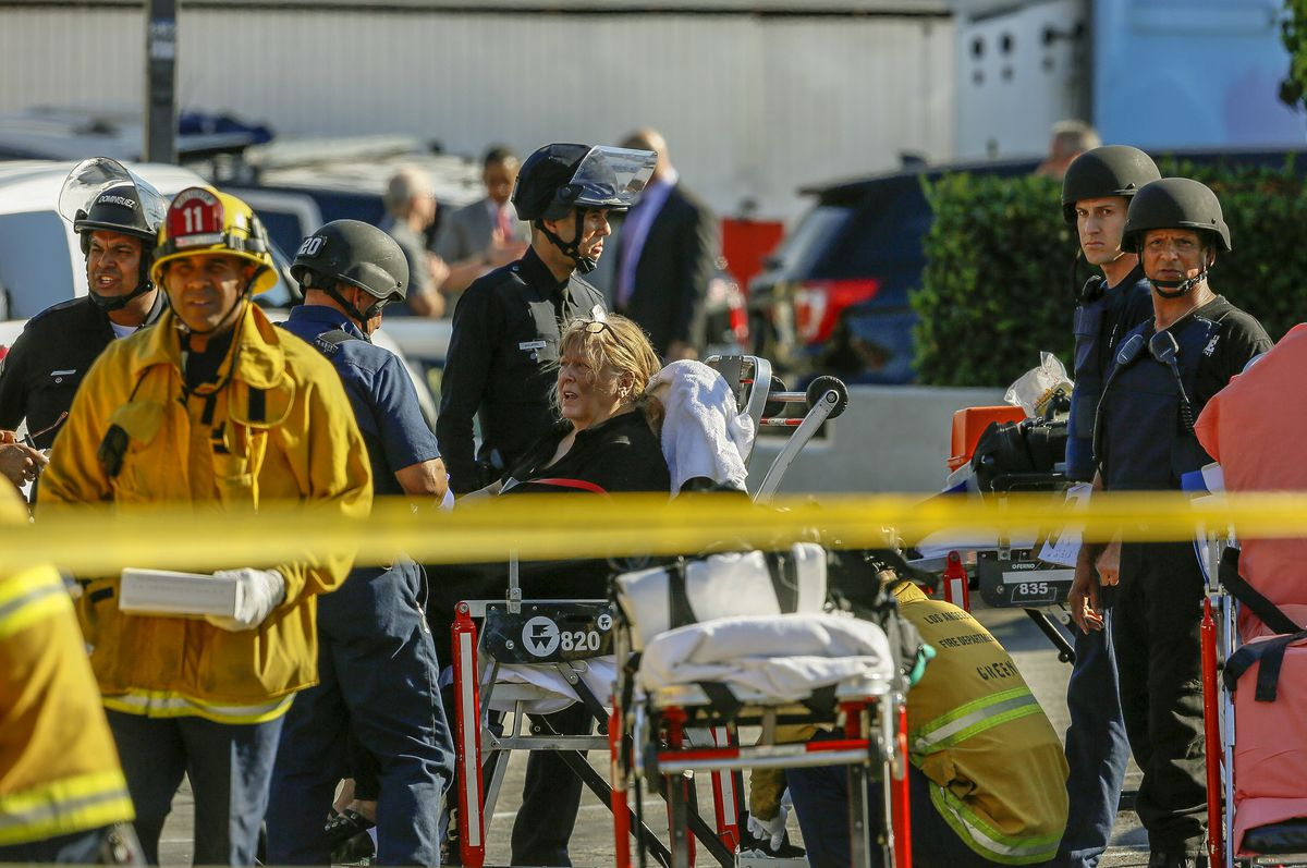 An unidentified woman is helped by paramedics at a triage area after a gunman held dozens of people hostage inside a Trader Joe's store in Los Angeles Saturday, July 21, 2018. | AP Photo/Damian Dovarganes