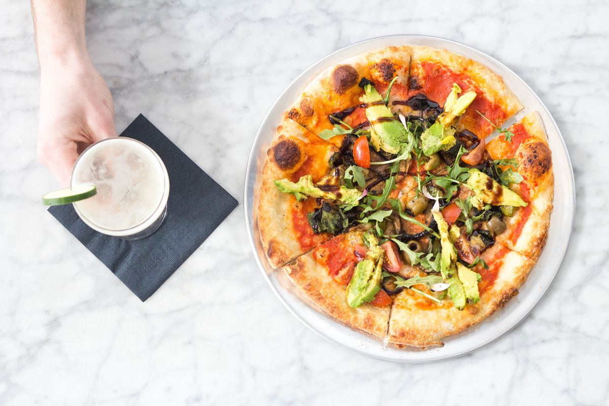 A hand holding a glass with a drink and pizza topped with vegetables seen from above