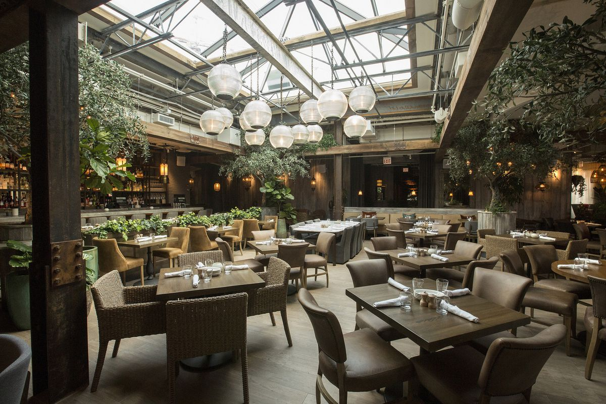 A large dining room with a glass roof and lots of green plants