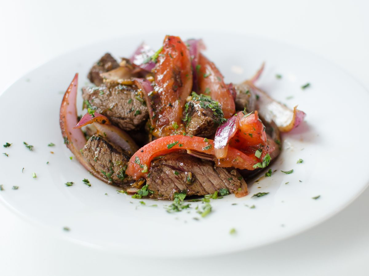 A white bowl on a white table is full of chunks of cooked beef, tossed with slices of red pepper and tomatoes. The dish is topped with green herbs.