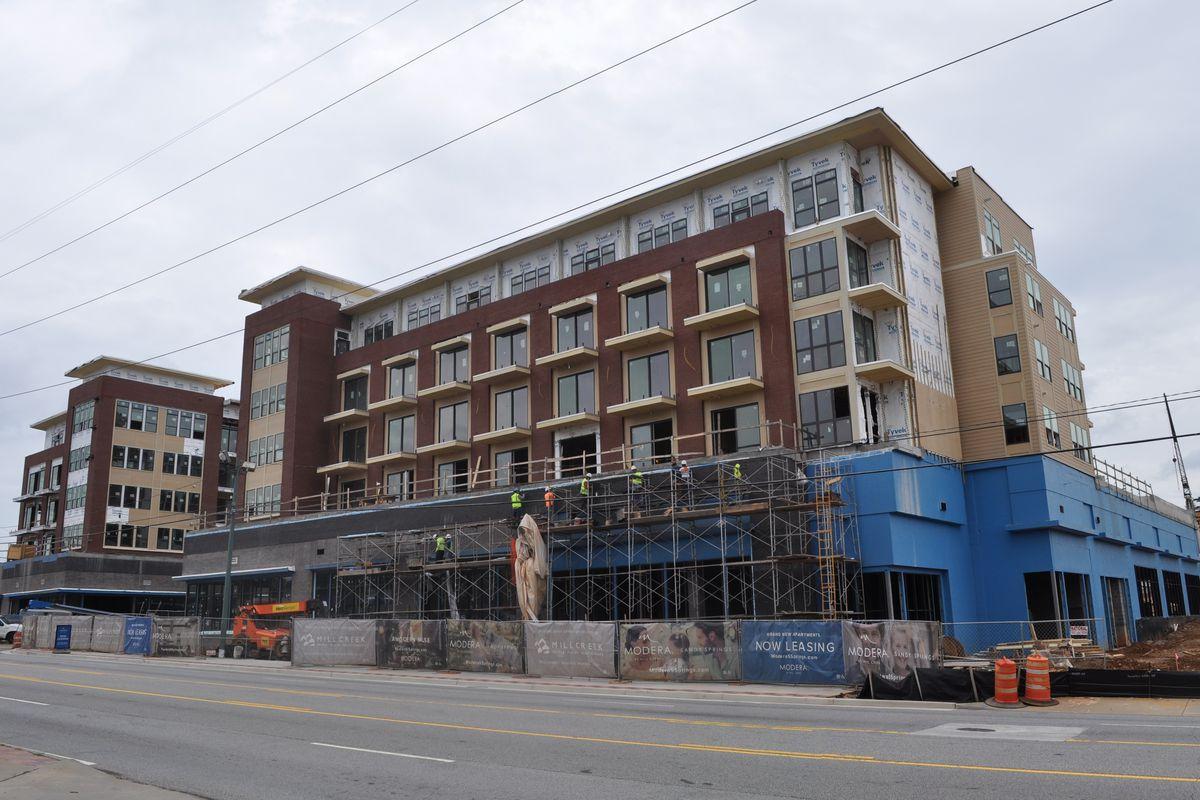 A five-story brick and siding apartment building atop retail podium.