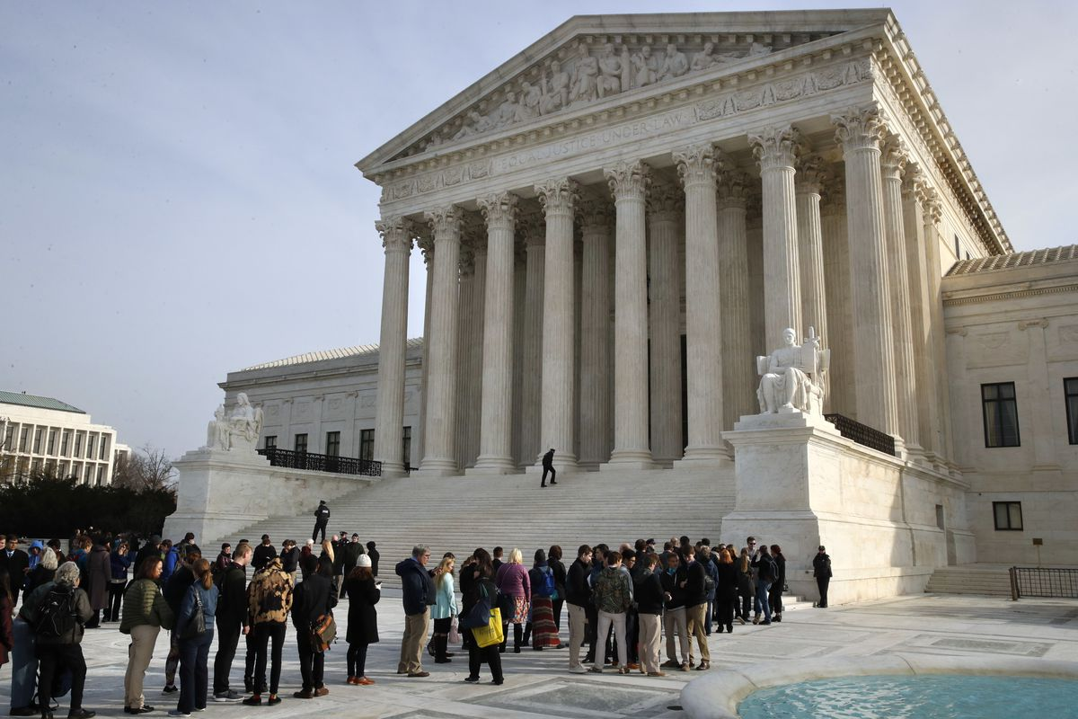 In this Dec. 4, 2017 photo, people stand in line to enter the Supreme Court in Washington. The Supreme Court is agreeing to decide the legality of the latest version of President Donald Trump's ban on travel to the United States by residents of six mostly