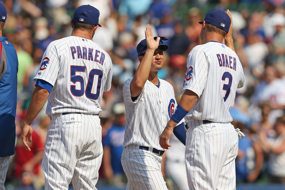 Blake Parker, Darwin Barney and Jeff Baker of the Chicago Cubs celebrate a win over the Arizona Diamondbacks at Wrigley Field in Chicago, Illinois. The Cubs defeated the Diamondbacks 3-1. (Photo by Jonathan Daniel/Getty Images)
