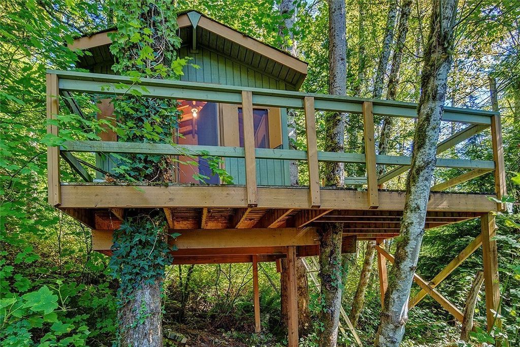 A green treehouse with a large deck