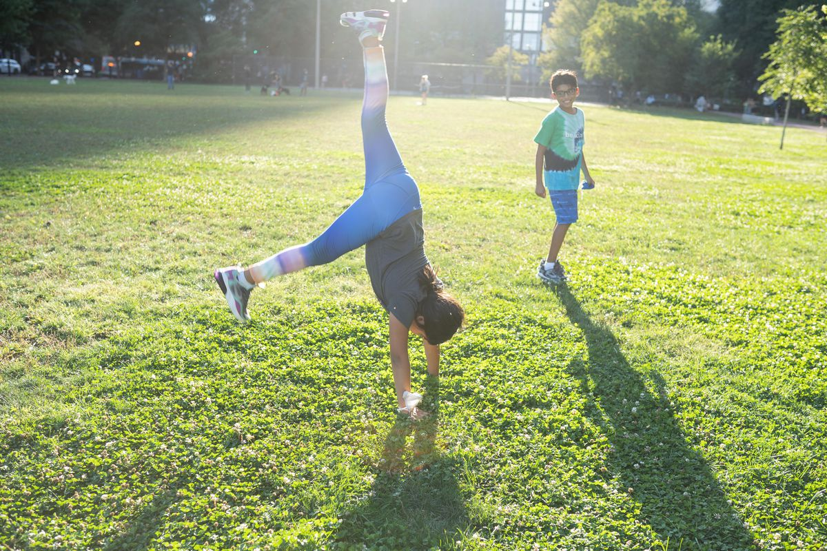 Celeste Hernandez, 8, a student at Franklin Fine Arts Center, performs cartwheels for the camera as her brother Juan Carlos, 10, also a student at Franklin Fine Arts Center, watches at Lake Shore Park in the Gold Coast neighborhood, Sept. 15, 2021.