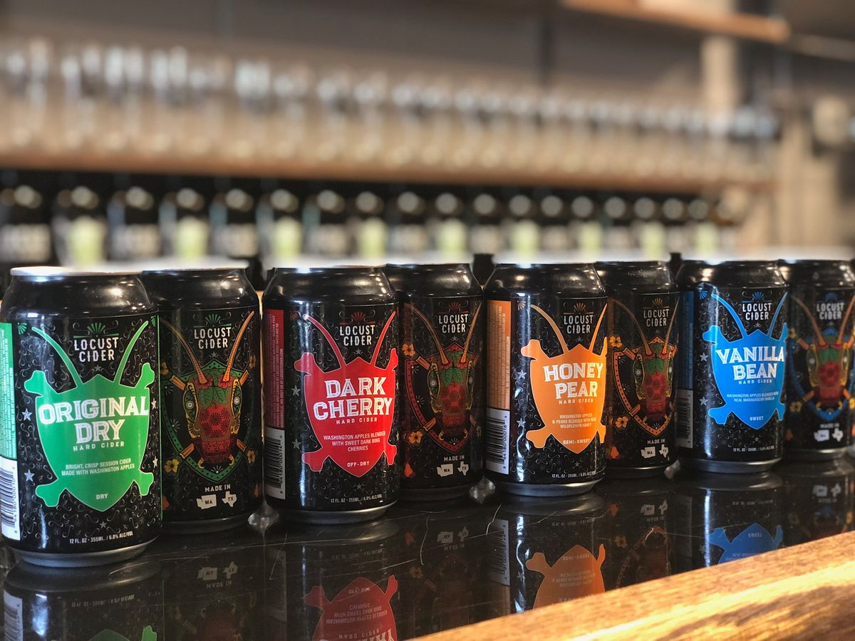A bar is lined with cans of Locust Cider, including flavors like original dry, dark cherry, honey pear, and vanilla bean.