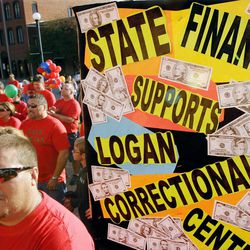 ADVANCE FOR USE MONDAY, APRIL 2 AND THEREAFTER - FILE - In this Oct. 13, 2011 filer photo, Logan Correctional Center employees, family members and supporters rally to protest against Illinois Gov. Pat Quinn's proposal to close the prison in Lincoln, Ill. The facts behind Quinn's proposed closures of state facilities and state employee layoffs are more complicated than recent harsh union ads acknowledge.