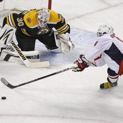Washington Capitals left wing Alex Ovechkin (8) tries to get his stick on the puck for a shot against Boston Bruins goalie Tim Thomas (30) during the first period of Game 2 of an NHL hockey Stanley Cup first-round playoff series in Boston, Saturday, April 13, 2012.