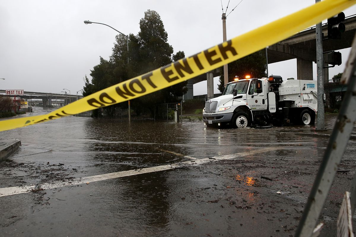 A San Francisco Department of Public Works street cleaner attempts to clear a drain that is causing an intersection to flood.