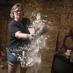 Shawn Baker, the owner of Tantrums, destroys a glass in a destruction room at Tantrums in Houston on Saturday, July 15, 2017. Tantrums is a business where people can let off steam by using bats, poles, golf clubs and sledge hammers to destroy TVs, mirrors, cups, sheets of glass and more. Baker started Tantrums after she was laid off from her job in the oil industry, and she said her business acts as therapy to some and fun for others.
