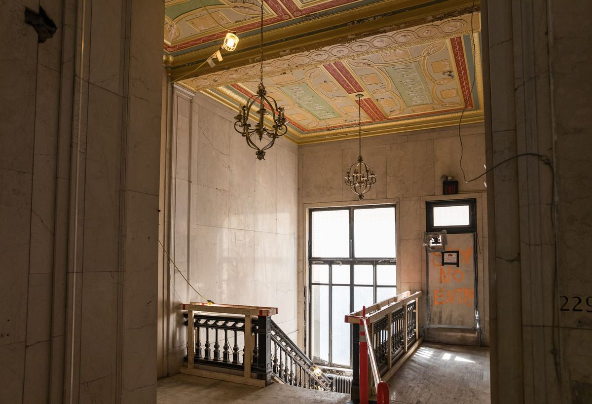 """An open door and a staircase.  The ceiling has ornate design and lights.  There is graffiti on a door that says """"Exit No Enter""""."""