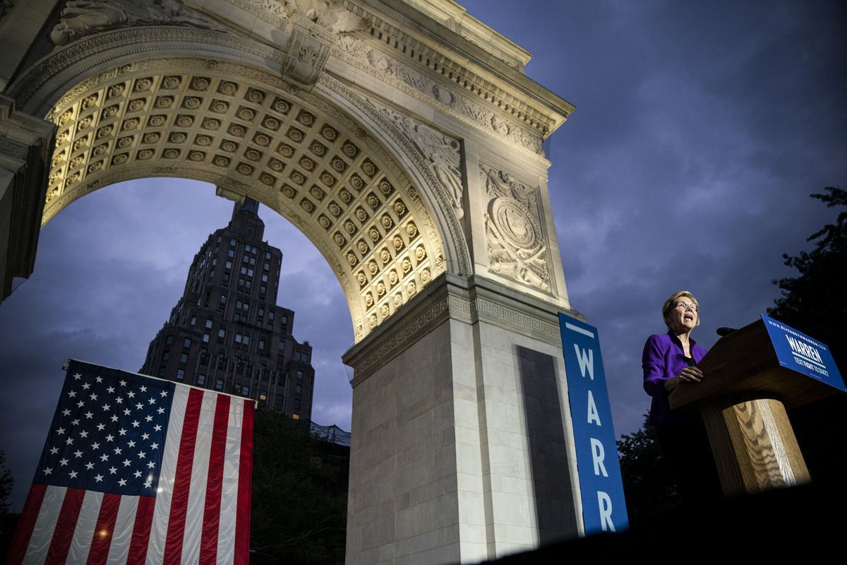 Sen. Elizabeth Warren speaks from a podium near the up-lit arch in New York's Washington Square Park.