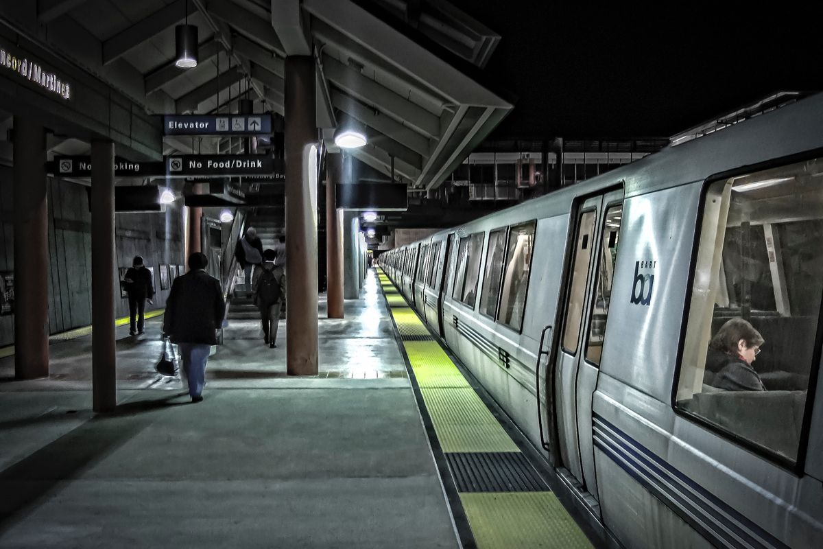 A BART train on a darkened platform with bright artificial lighting.