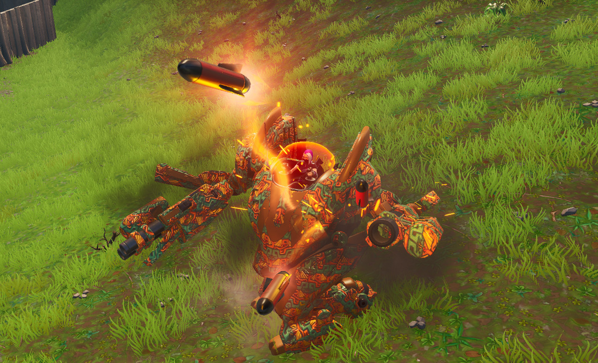 A mech fires several rockets while standing in a field of grass