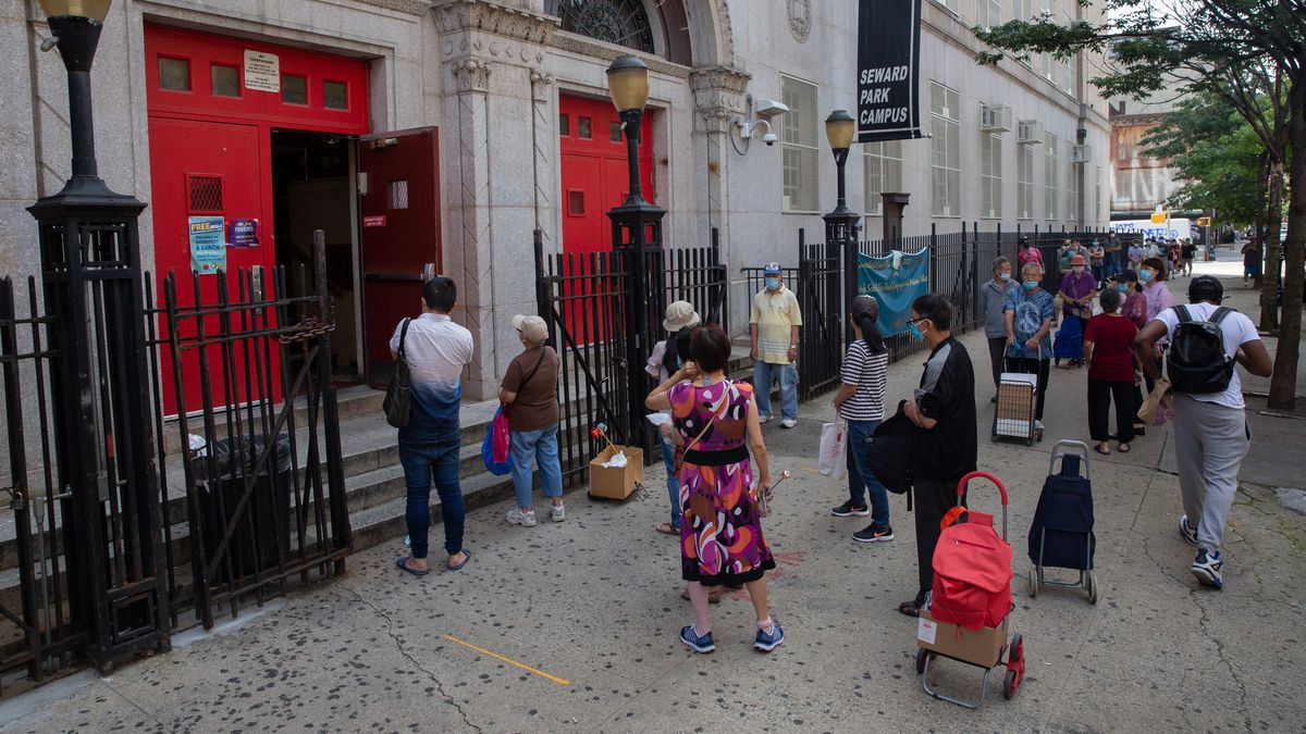 People pick up grab-and-go lunches from Seward Park Campus in the Lower East Side, Aug. 21, 2020.