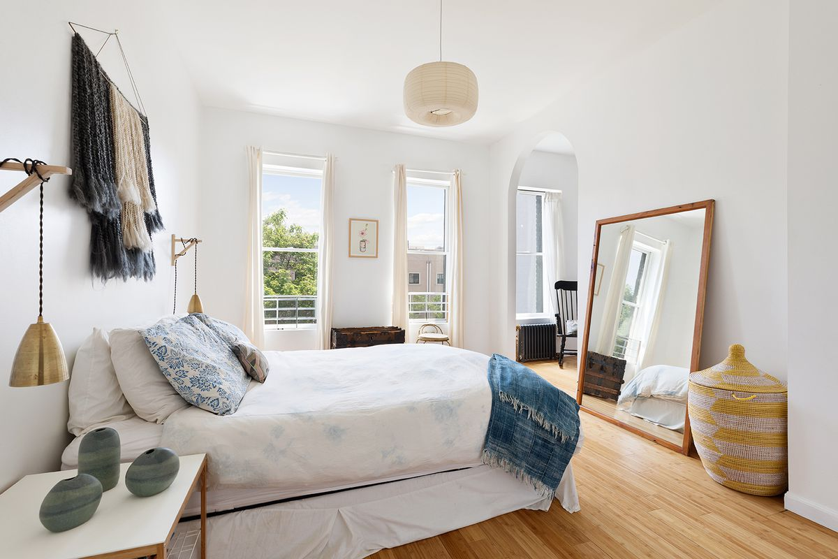 A bedroom with a small bed, large windows, hardwood floors, and white walls.