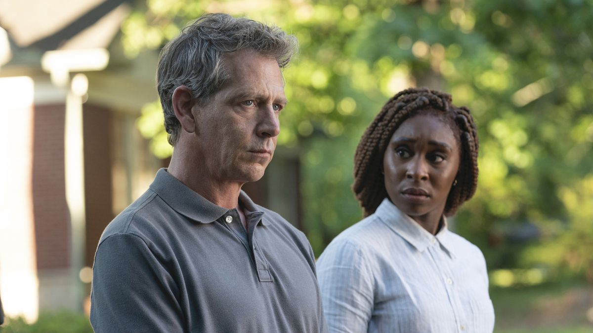 Ben Mendelsohn and Cynthia Erivo stand outside in front of a tree-lined backdrop in HBO's The Outsider.