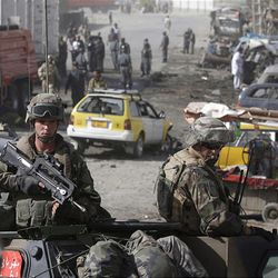French ISAF soldiers guard the scene of a suicide car bomb attack on the outskirts of Kabul Tuesday.