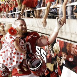 Utah Utes offensive linesman Tony Bergstrom (70) and his daughter shakes hands with the students after the Utes' season-opener at Rice Eccles Stadium in Salt Lake City  Thursday, Sept. 1, 2011.