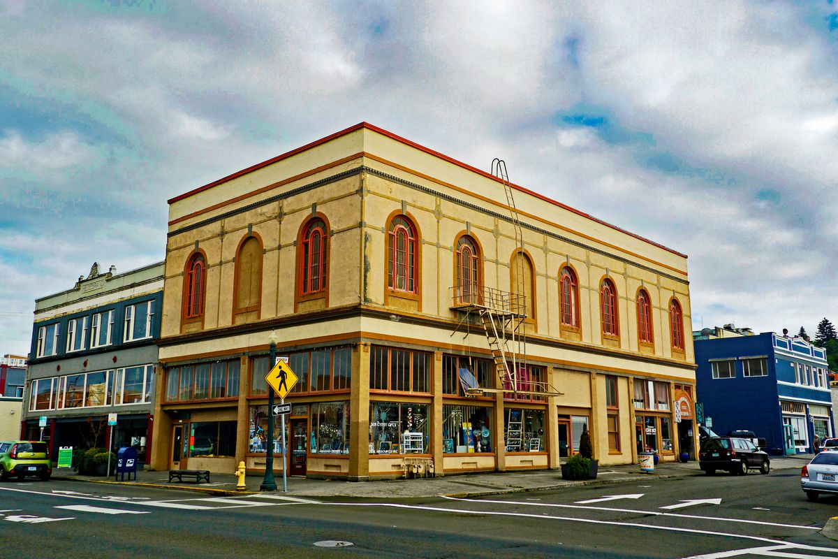 A two-story yellow building sits at a street corner.