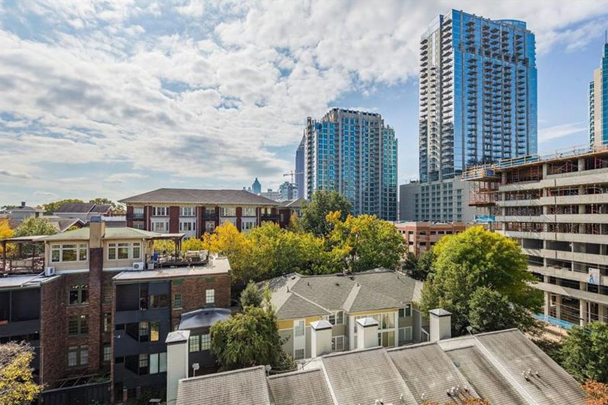 Panoramic view of building rooftops and glass high-rise buildings.