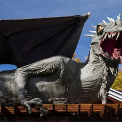 A dragon created by Ammon Smith is perched atop his home in Salt Lake City on Thursday, Oct. 13, 2016, in preparation for Halloween.