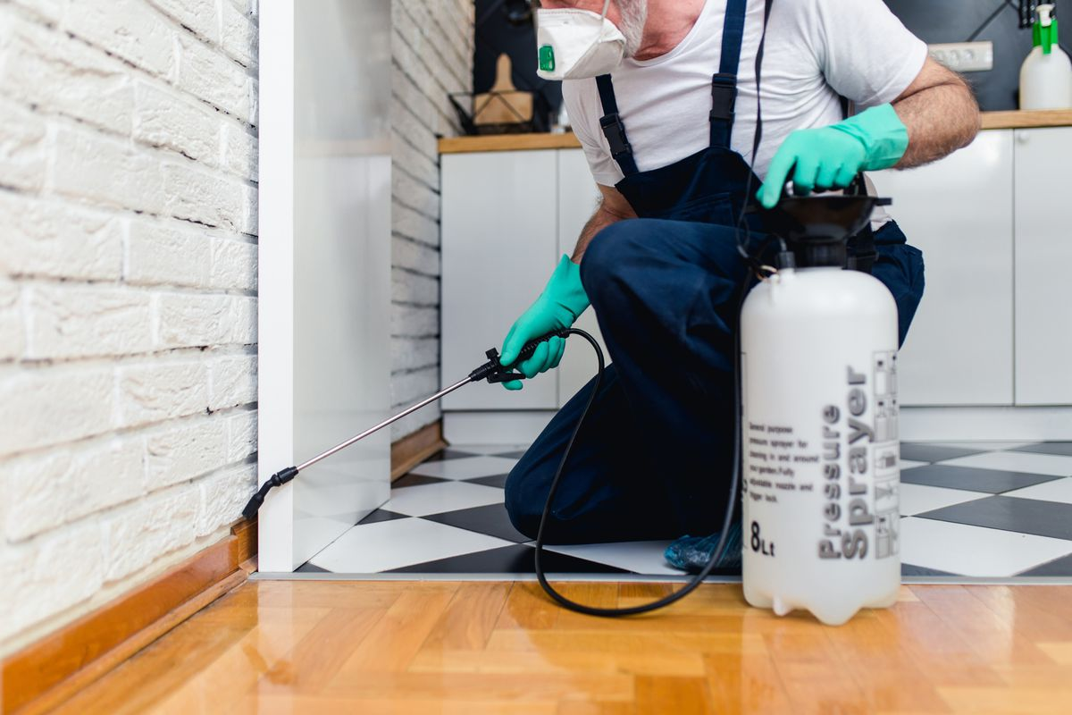 A pest control specialist wearing blue overalls and a white shirt kneels on a checkerboard floor to use a black wand to spray pest control solution in the interior of a home.