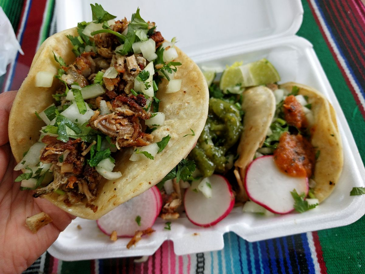 Three meat filled tacos in a styrofoam container, one being pulled out by a hand.