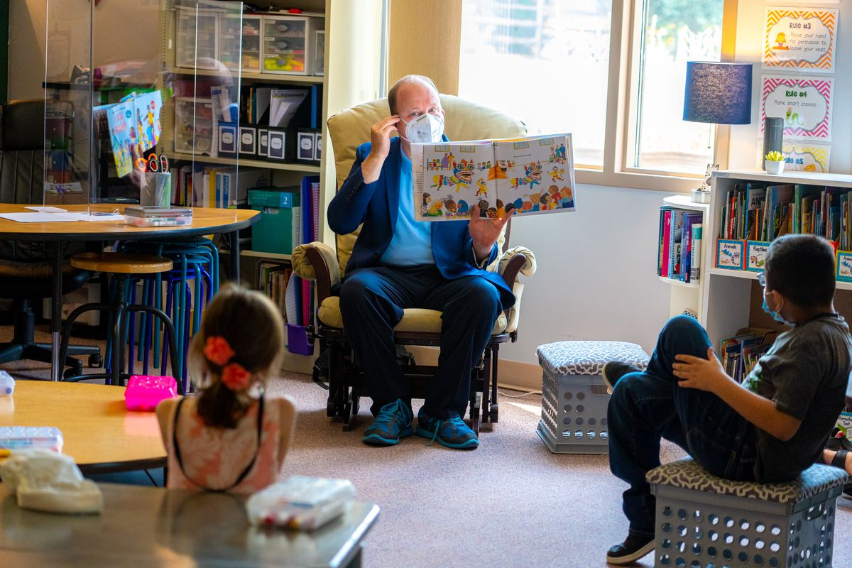 Colorado Gov. Jared Polis reads a story to young schoolchildren in a classroom while wearing a mask during the COVID-19 pandemic.