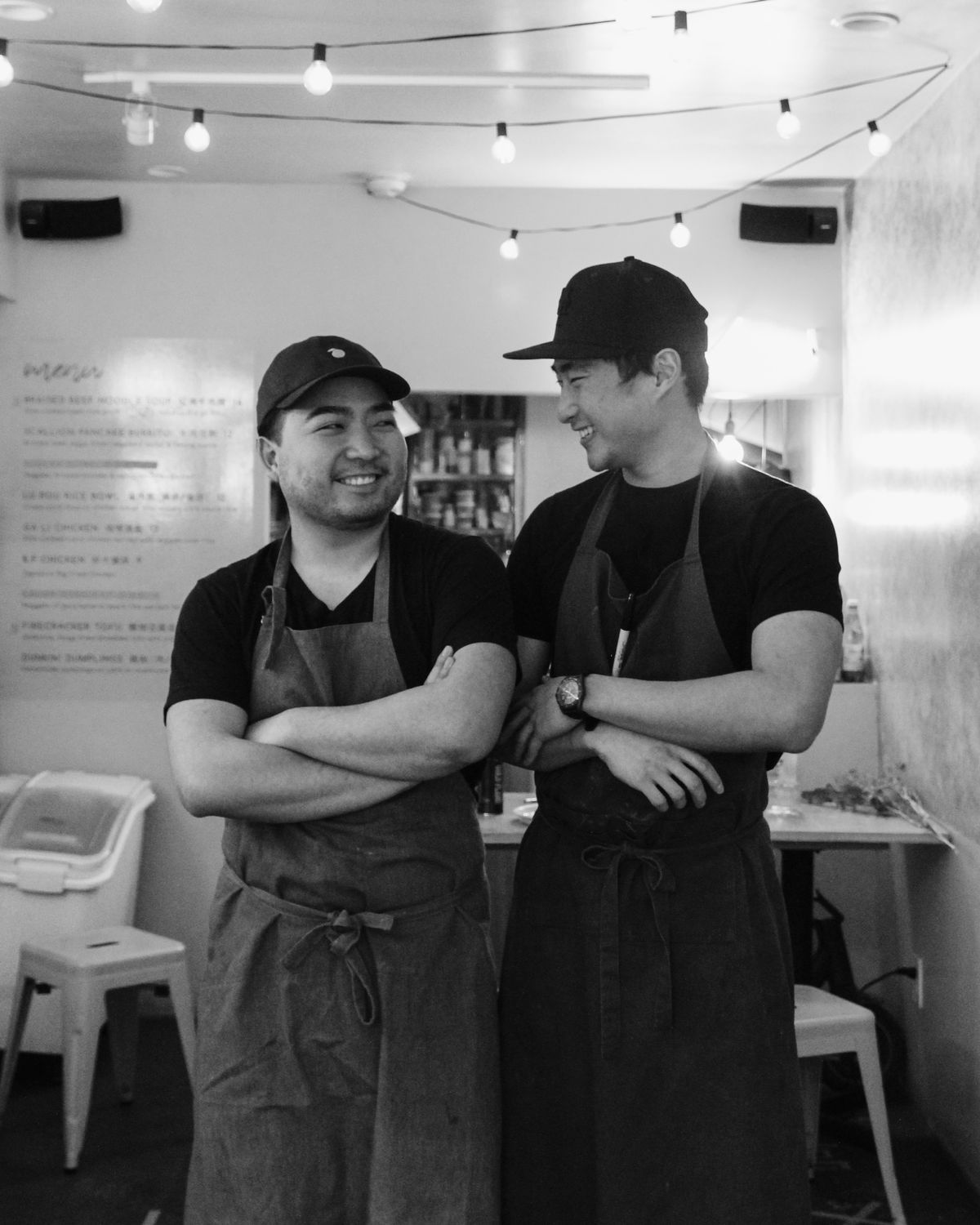 Two chefs wearing aprons in a black and white photo looking at each other and smiling