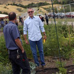 James Wolf, garden steward, center, tours the plots at the dedication of the Popperton Plots community garden in Salt Lake City on Friday, Aug. 22, 2014.