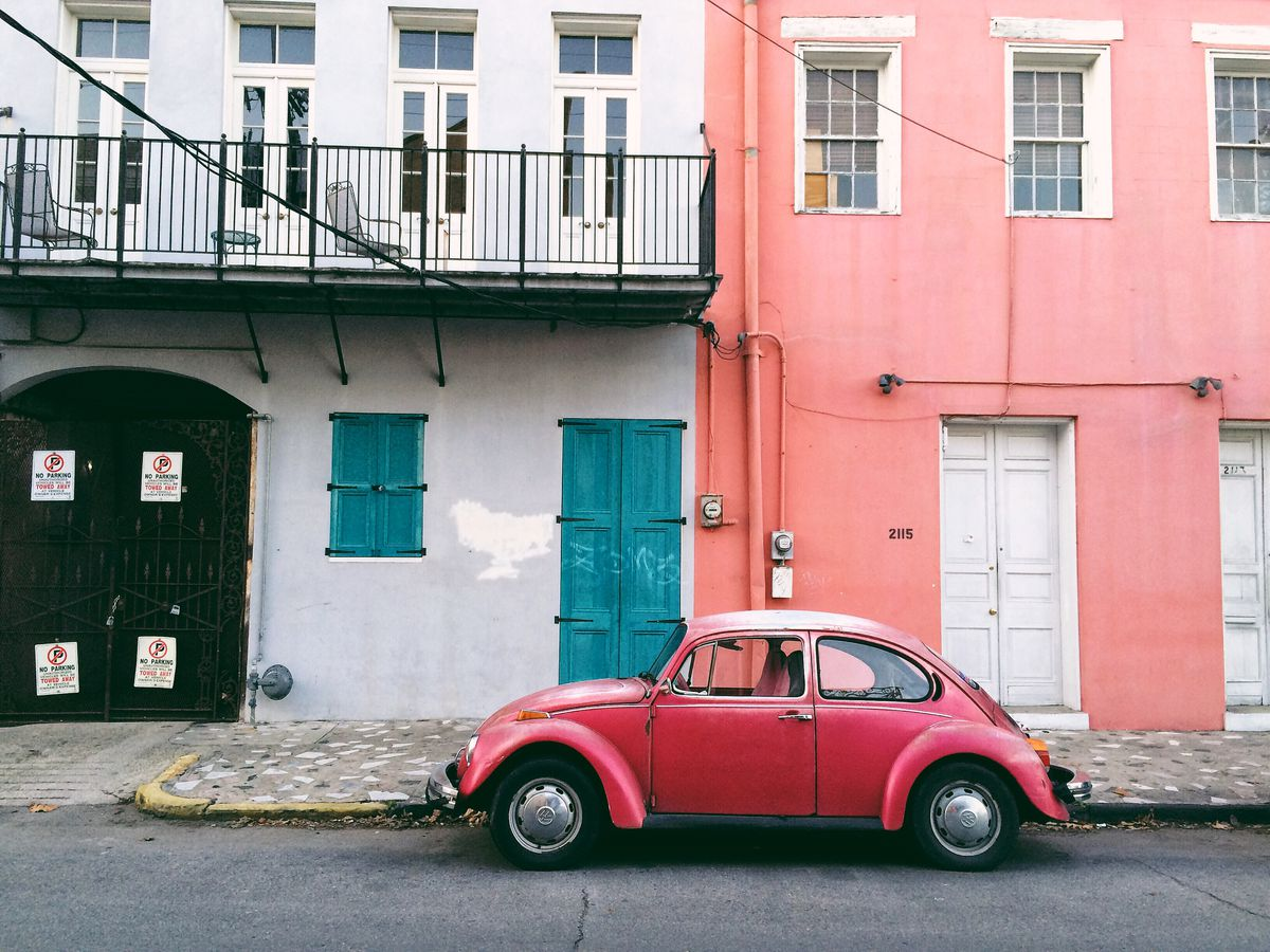 A red car on a quaint street in the French Quarter.