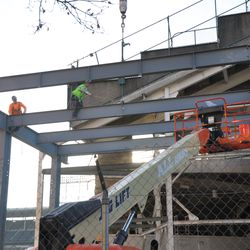 Steel beam being positioned into place in the right-center field patio -