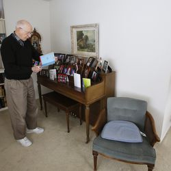 Roger Thompson, 99, looks over a birthday card at his home in Salt Lake City Friday, Dec. 3, 2013.