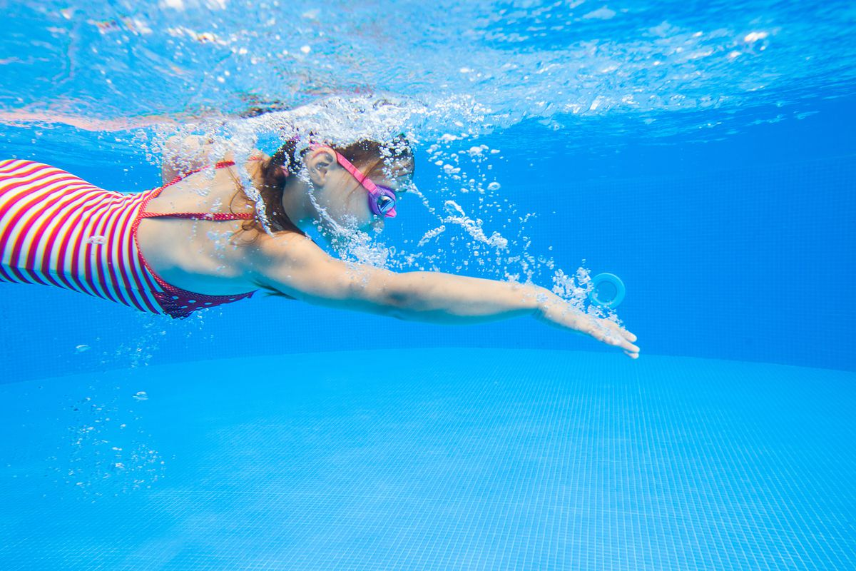 A young girl swimming in a pool
