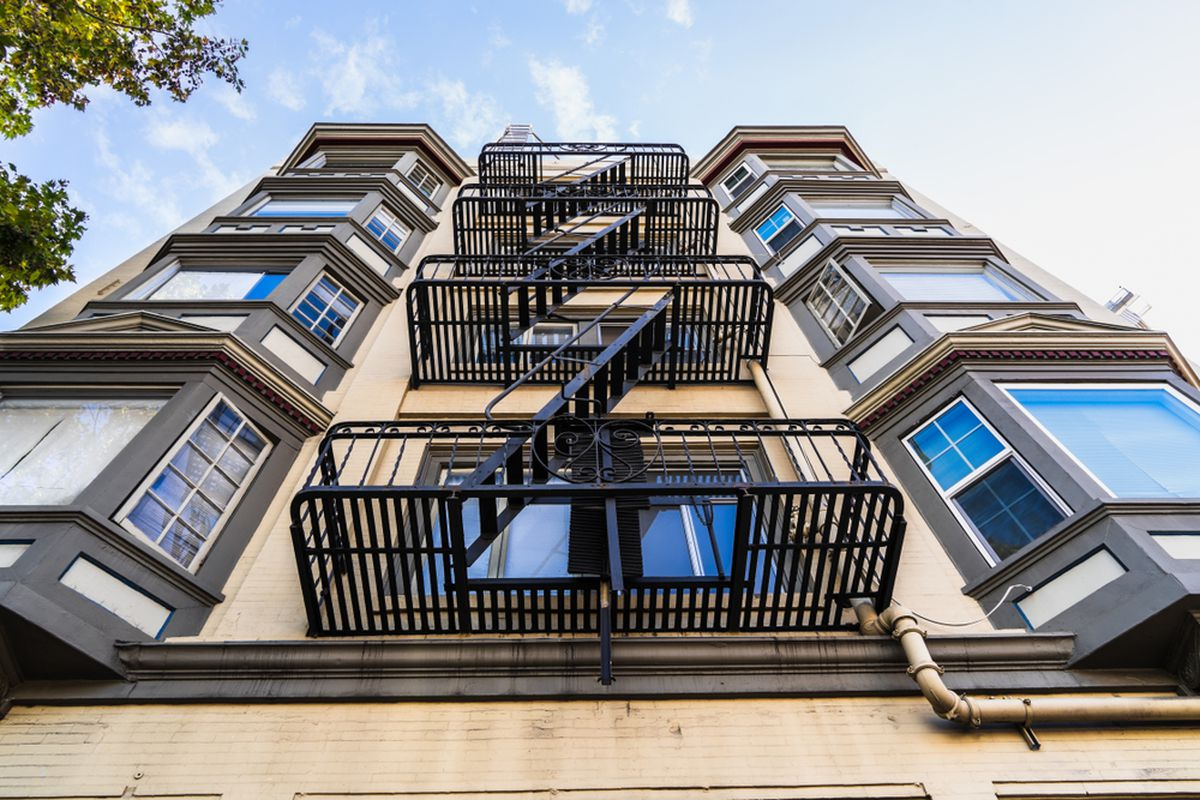 Exterior view of multifamily residential building, with old metal fire escapes and bay windows.