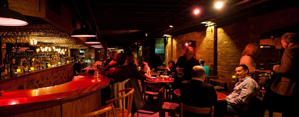 A dimly lit bar filled with people and surrounded by brick and wood.