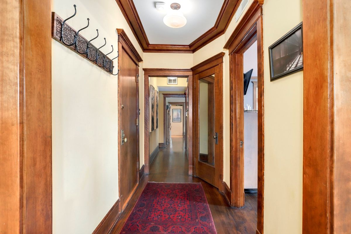 A long hallway with rows of wood doors topped by wood trim.