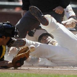 San Francisco Giants' Melky Cabrera, right, slides into home plate to score the Giants' first run as Pittsburgh Pirates catcher Rod Barajas, left, looks on during the first inning of their baseball game in San Francisco, Friday, April 13, 2012. Cabrera scored after Giants' Buster Posey doubled.