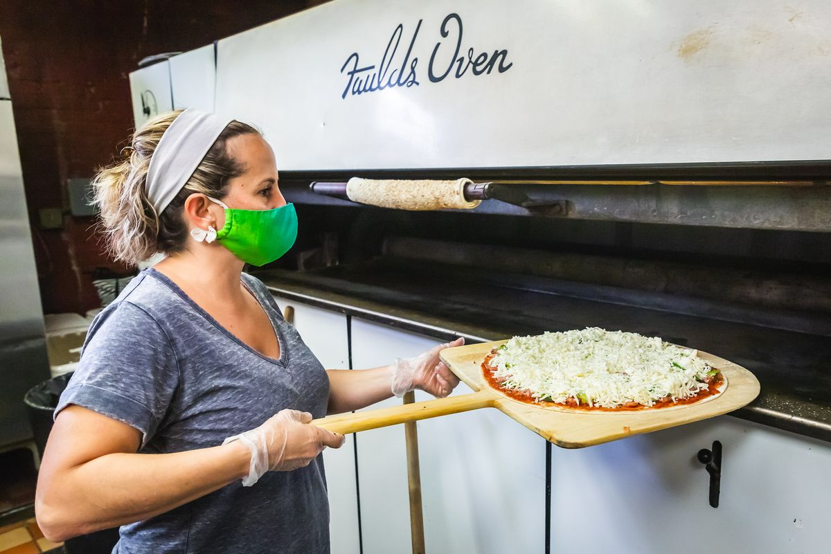 A masked person puts a pizza into an oven.