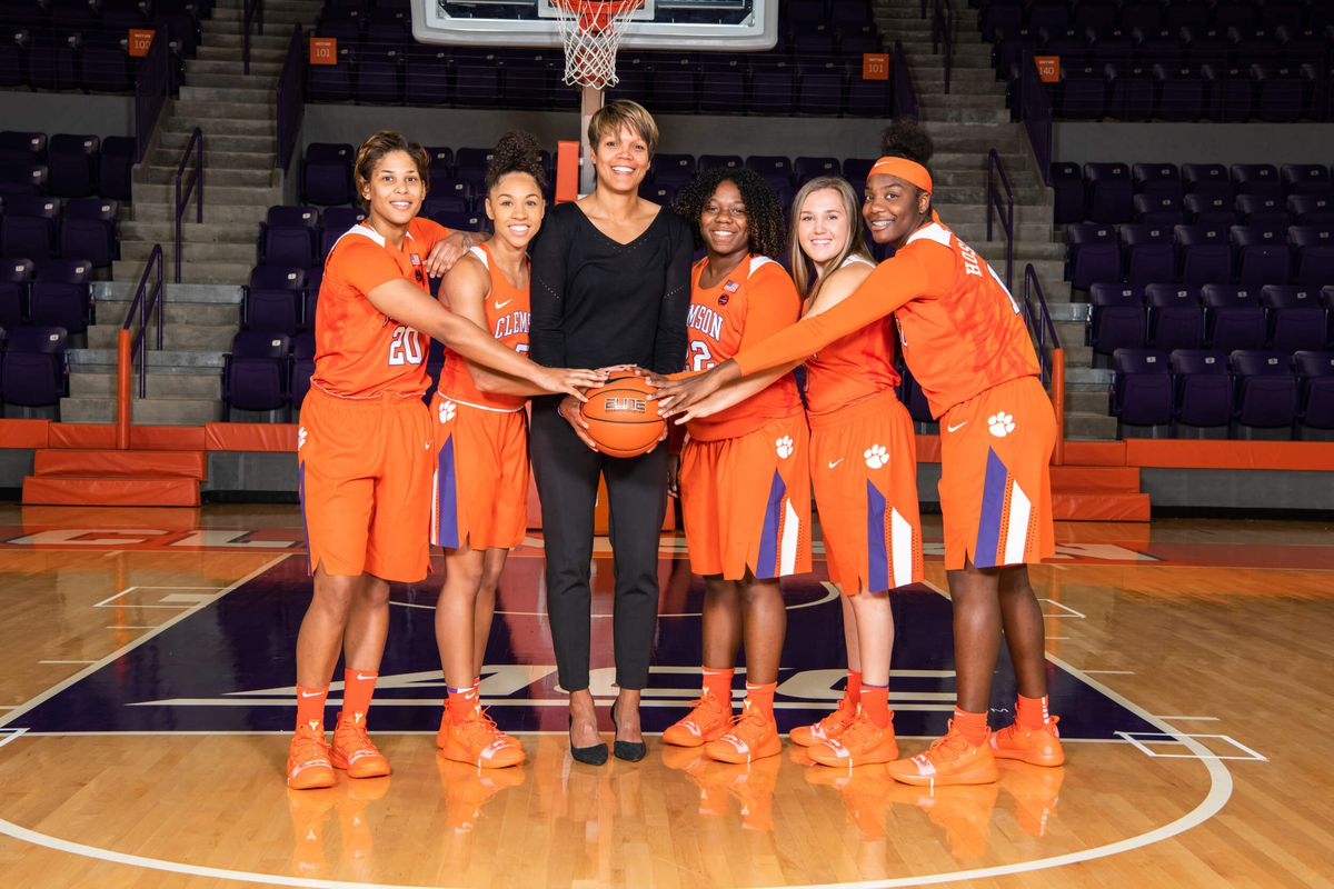 Coach Shimmy Gray-Miller holds a basketball with five players on the Clemson team.