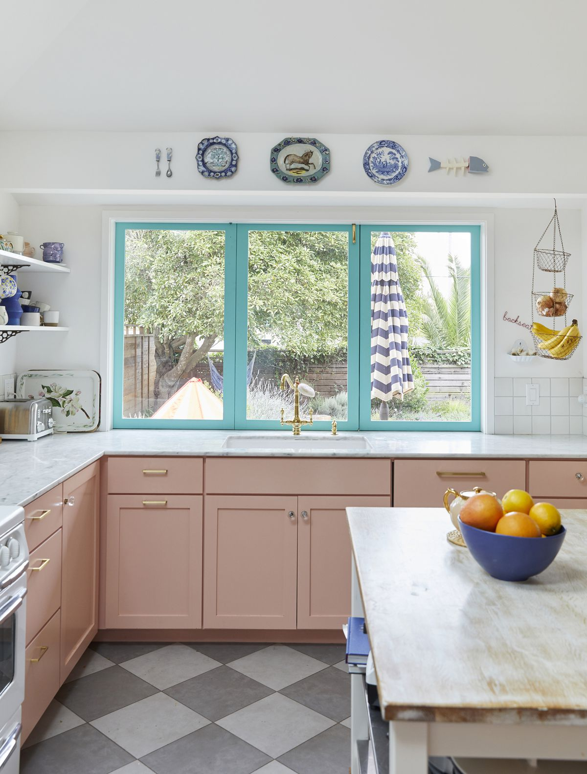 A kitchen with a triple paned window. The kitchen cabinets are painted pink. There is artwork above the windows and a hanging fruit basket. The floor is tiled with black and white diamond patterned tiles.