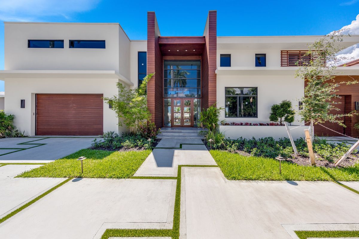 Out front of a beautiful tropical modern home in Fort Lauderdale, with a huge glass foyer, wooden garage and modern features
