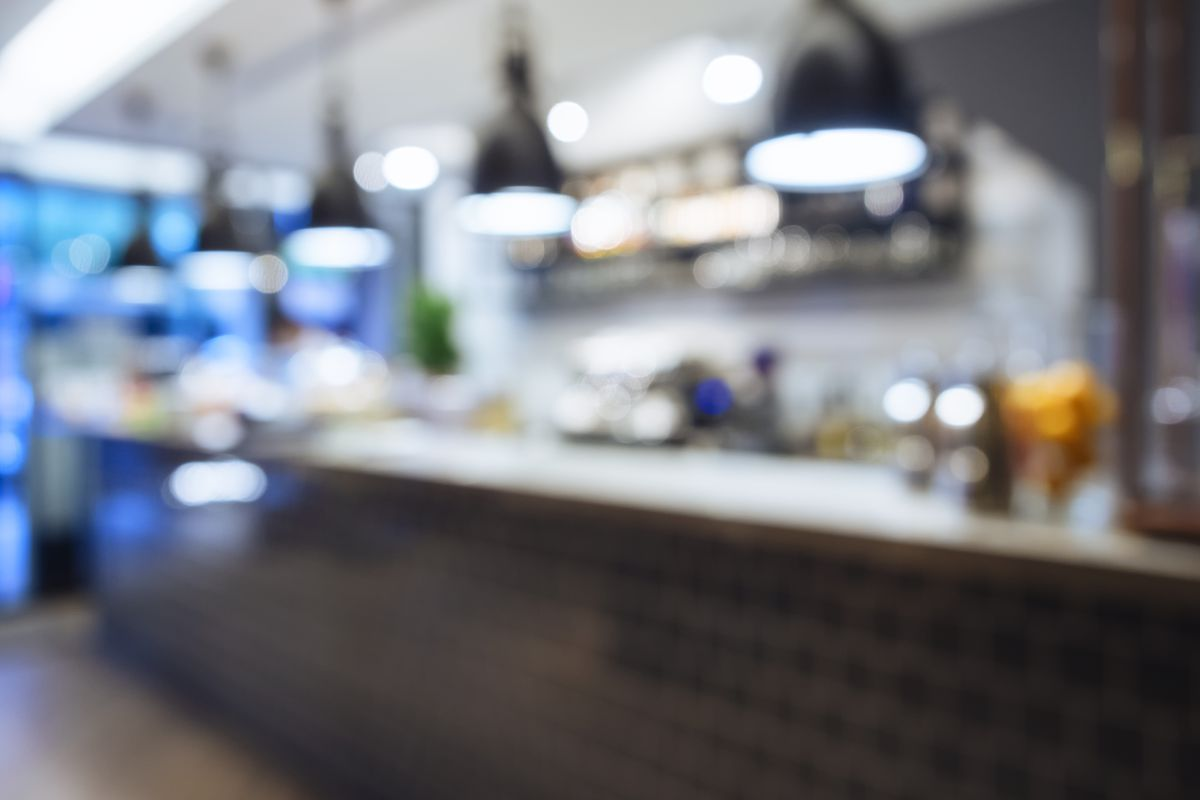 A blurry photo of the inside of a restaurant kitchen, with lamps hanging above a counter