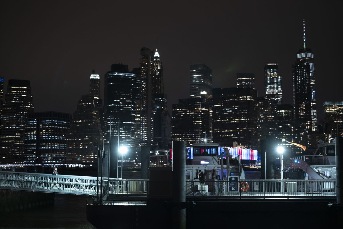 """A deckhand, left, walks alone on a gangplank to a ferry in Brooklyn Bridge Park, Tuesday night, April 14, 2020 during the coronavirus pandemic in New York. Known as """"The City That Never Sleeps,"""" New York's streets are particularly empty during the pandemic. (AP Photo/Mark Lennihan)"""
