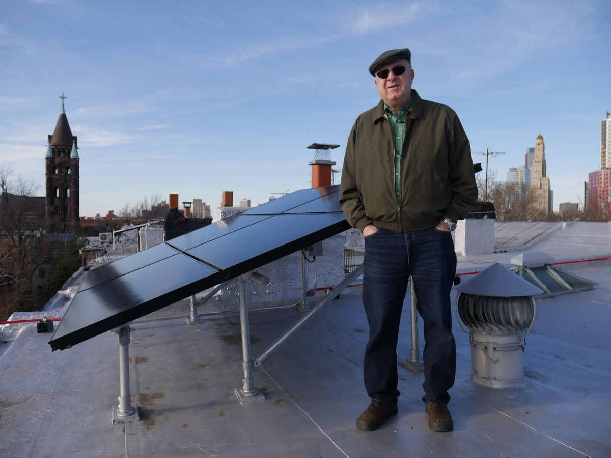 A man stands on a roof next to sloping black solar panels. The man is in outerwear. There is a city skyline in the distance.