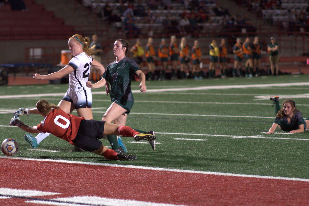 Dixie State's Whitley Johns (middle) tucks home her team-high fifth goal of the year just past the diving Adams State goalkeeper in the Trailblazers' 4-0 win Friday night at Trailblazer Stadium.