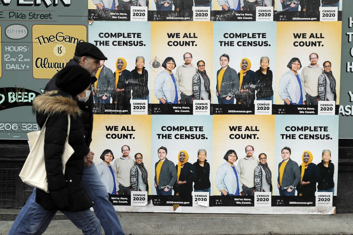 In this April 1, 2020, file photo, pedestrians in Seattle walk past posters encouraging participation in the 2020 Census.