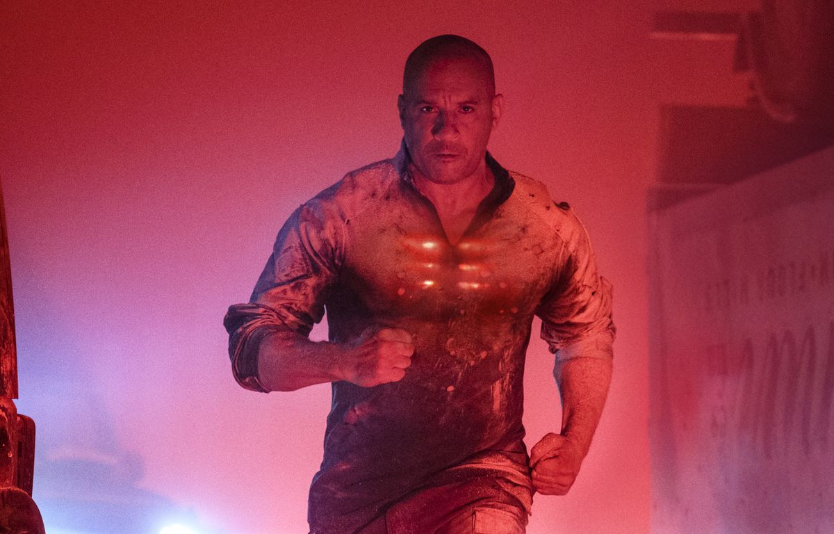 Vin Diesel runs toward the camera, looking determined, his chest glowing red, in a red-lit photo.
